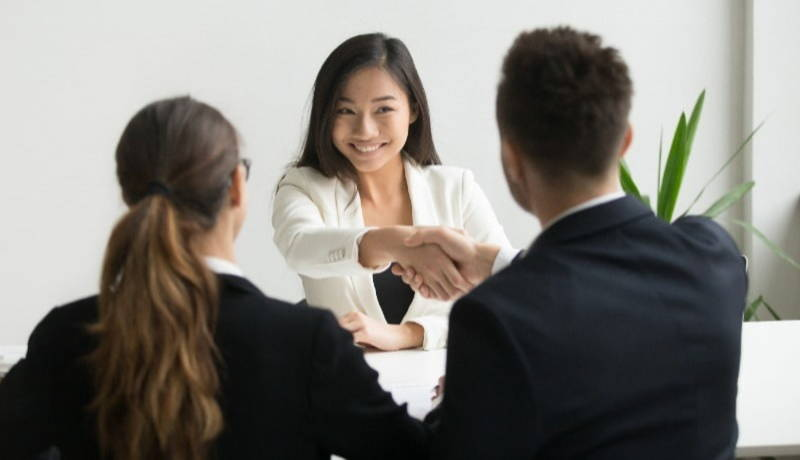 Woman shaking mans hand at desk